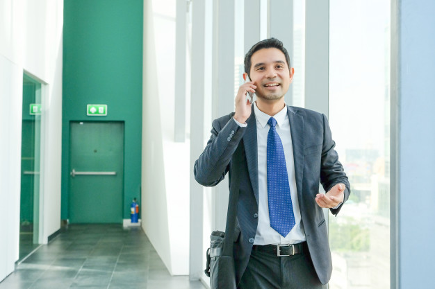 Business -man -talking -smart -phone -with -happy -smiling -face -while -walking -by -window _7190-43
